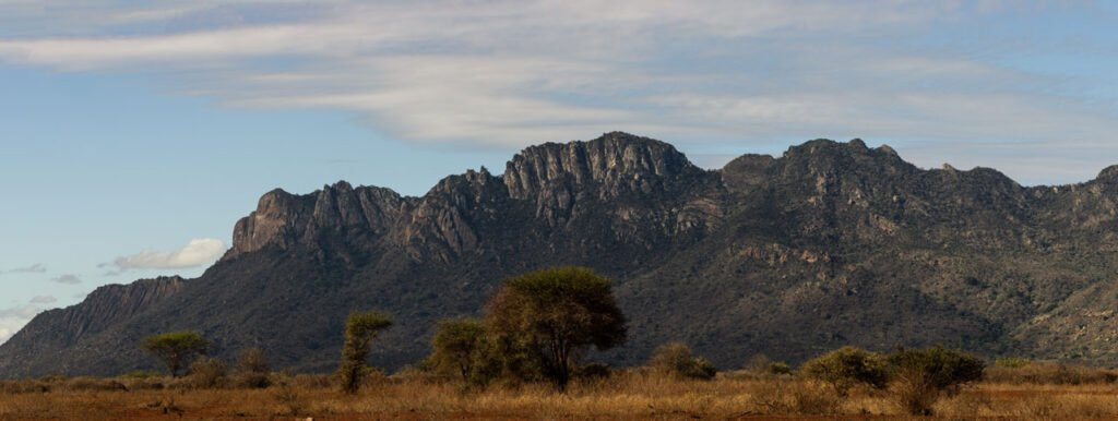 15 panel panorama of large mountainside within Tsavo West National Park, from the Rhino sanctuary.
