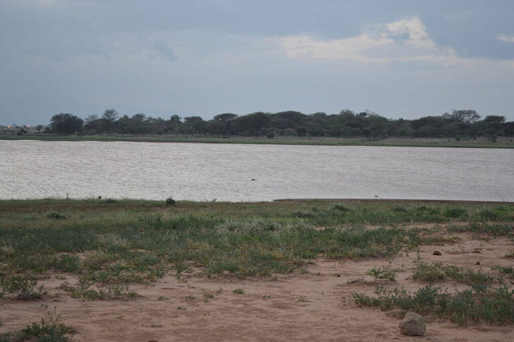 Aruba Dam, on the Voi River, located next to the Ashnill Aruba Lodge (in the background), as viewed from the east during the evening, in the Tsavo East National Park, Kenya